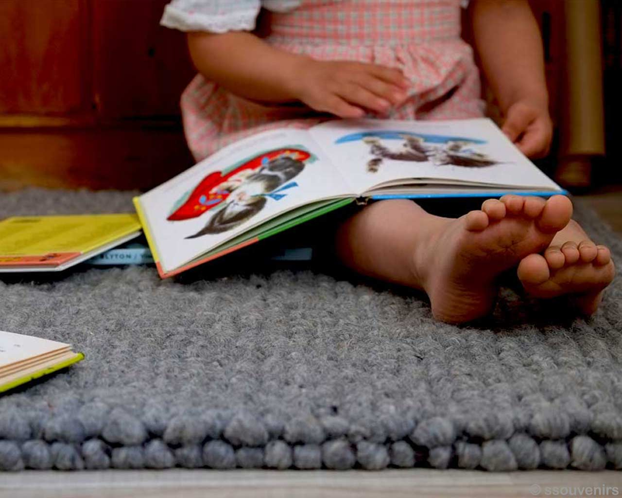 child reading textbook handmade woollen rugs india
