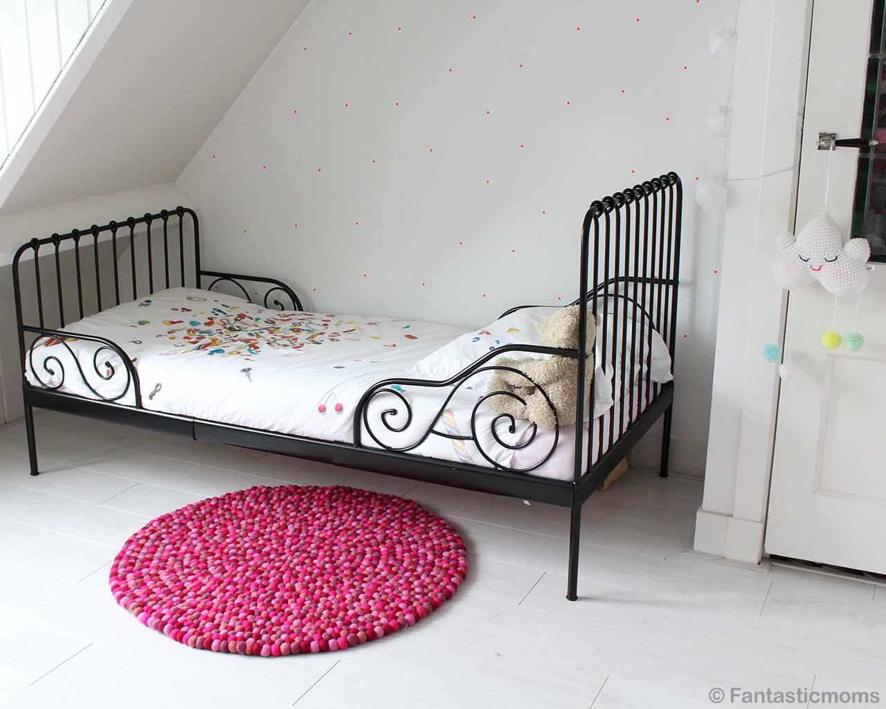 hand knotted black steel bed with white bedsheet made by nepalian contemporary round area rug